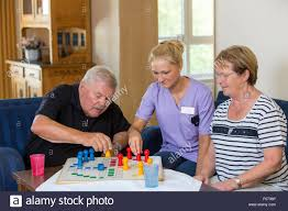Home Nurse by Elderly Care In A Nursing Home Nurse Plays With Two Patients A