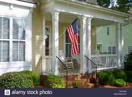 an american flag hangs from a front porch in a neighborhood of