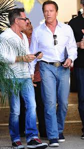 arnold schwarzenegger in white top and blue jeans with mystery