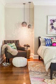 metallic pendant lights hang above a gray armchair in the corner