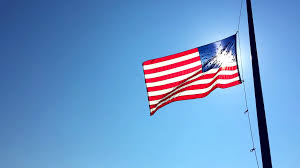 Flag Half Mass Today American Flag Flies At Half Mast Backlit By The Sun In Bright Blue