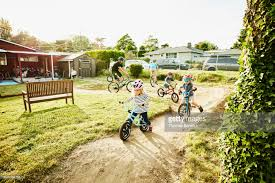 kids riding bmx bikes with dads on backyard dirt track on summer