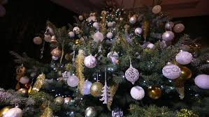 christmas tree decorated with lights balls flowers ribbons and