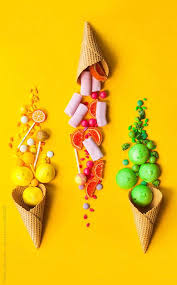 different kind of colorful candies in ice cream cone on yellow