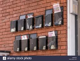 black metal mailboxes hang on a red brick wall outside an