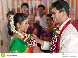 indian hindu groom looking at and exchanging garland in