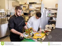 chef and cook cooking food at restaurant kitchen stock photo