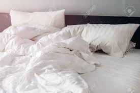 bed and white pillows with wrinkle blanket in bedroom from