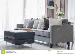 modern grey sofa with pillows and black table in living room stock