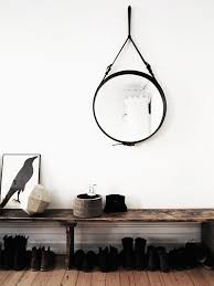 your round mirror hanging from a leather strap interior