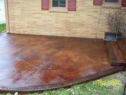 dark brown wooden stained concrete patio floor with cream brick