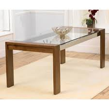 rectangle glass top table with brown wooden frame and legs placed