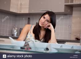 young woman sitting at the dining table in the kitchen and relaxed