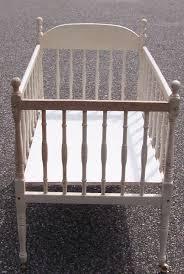 antique white wooden baby crib on wheels