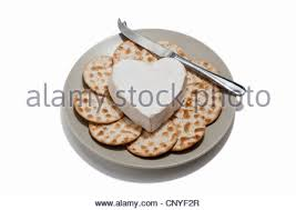 heart shaped crackers a heart shaped cheese with crackers and cheese knife on a plate