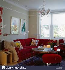 living room l tables nest of tables beside red l shaped sofa in small townhouse living