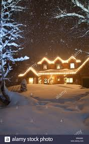 log home decorated with lights with snow falling