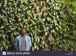 a man standing in front of a wall covered in climbing plants and