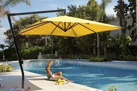 square yellow fabric patio umbrella with black metal base over