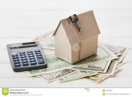 model of cardboard house with key calculator and cash dollars