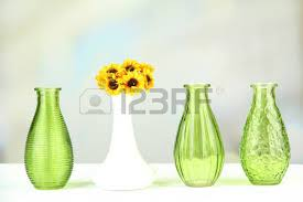 decorative shelf on white brick wall with flowers in vase on