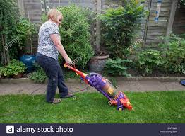 woman vacuuming the grass lawn with a dyson vacuum cleaner stock
