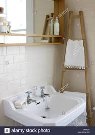 Washbasin In White Tiled Bathroom With Wooden Towel Ladder Stock