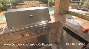 outdoor kitchen with a fire pit and bbq grill in brandon florida