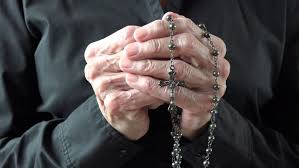 holding a catholic rosary or cucifix and praying to