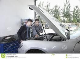 garage mechanic explaining to customer and looking at car with car explaining hood mechanic open