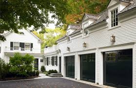 traditional style home features black garage doors by patrick