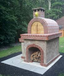 a beautiful red brick pizza oven on a pizza oven base with a