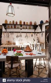moroccan kitchen with dark wood shelving hanging pans and