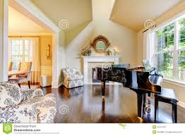 cream yellow living room with piano and fireplace royalty free