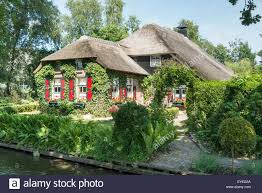 Giethoorn Holland Homes For Sale by Old Farm House With Lots Of Flowers And Plants In Giethoorn The