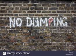 no dumping writing painted on an urban brick wall in the south