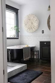 bathroom with white subway tiles and black clawfoot tub also