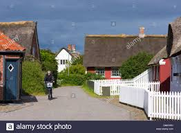 woman cycling past traditional thatched cottage houses on fano