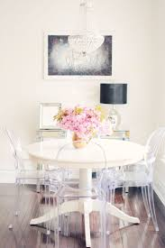 best 25 glass round dining table ideas on pinterest glass a small but chic dining room featuring a cream round wood table luctie louis ghost style chairs a mirrored chest and a crystal chandelier home
