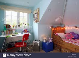 novelty fairy lights above wooden bed in pastel blue teenage attic