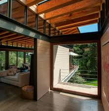 elevated ceilings w exposed hardwood beams providing excellent cozy warm breezy home interior design with clerestory windows and steel truss construction also bleach wood floor and exposed timber beam ceiling skylight