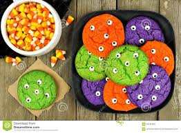 plate of halloween monster eyeball cookies with candy corn stock
