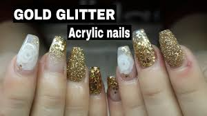 coffin shaped acrylic nails with gold glitter and 3d encapsulated