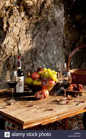 italian red wine and a bowl of fruit on a rustic table umbria