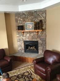 natural stone of corner fireplace design with wooden mantle shelf