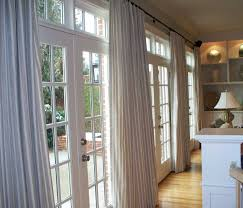 long cream drapes on the glass sliding door with white wooden