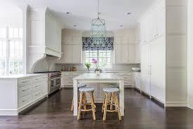 two kitchen islands with black and white stools transitional