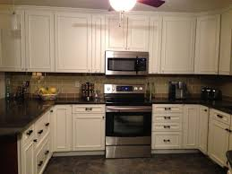 white off cabinet applied on the black ceramics floor kitchen natural kitchen counter backsplash ideas with black top table it also has white lamp on the