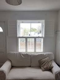 tier on tier plantation shutters fitted to sash window in living