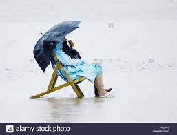 Chairs On A Beach A Man And A Woman Sitting In Deck Chairs On A Beach In Rain Coats
